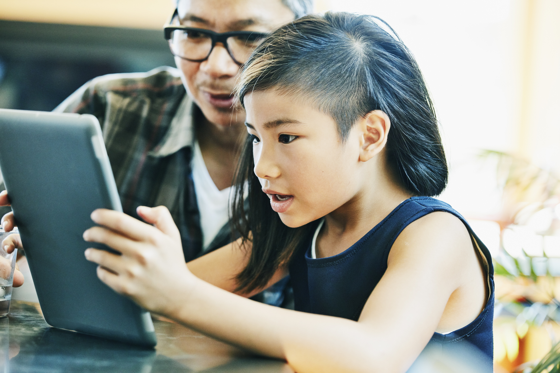Young girl looking at video on digital tablet with father at kitchen table