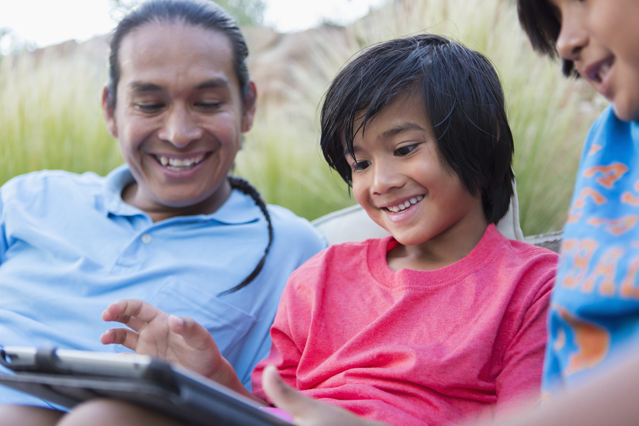 Family using digital tablet outdoors