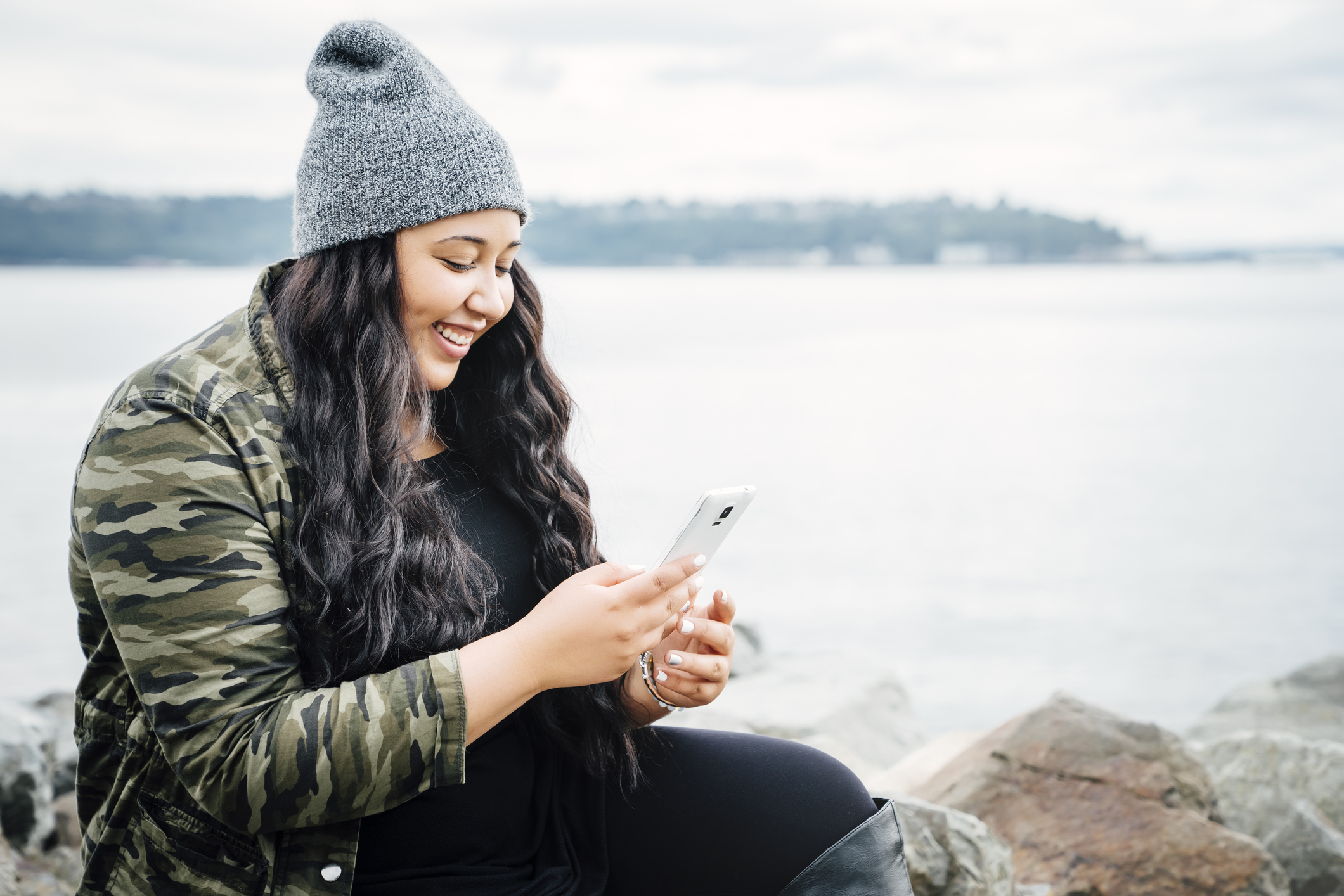 indigenous woman uses her phone. She smiles while sitting on the side of a lake.